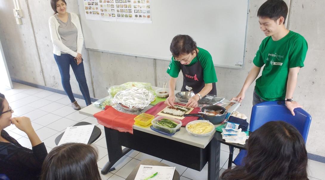 メキシコの大学生に寿司づくりのデモンストレーションを行う日本語教育ボランティア